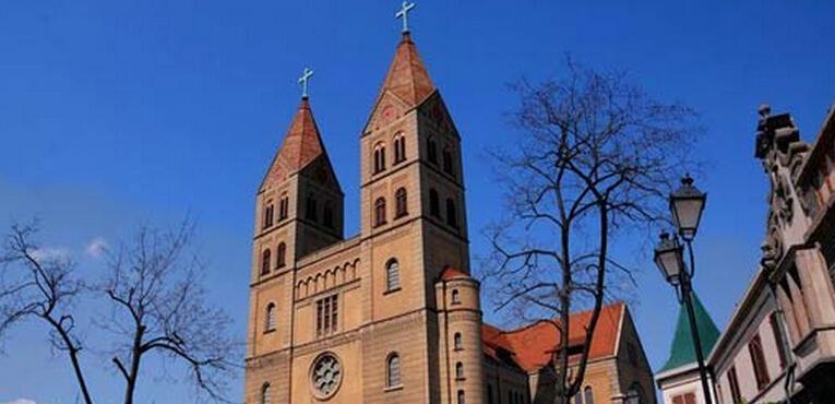 青岛圣弥爱尔大教堂的教座占地面积约2470平方米,总长度为65米,十字形耳堂长34米,檐高18米。整个建筑是由黄色的花岗岩和钢筋混凝土砌成的,搭配红色的尖顶,醒目而漂亮。 青岛天主教堂坐落地地势较高,所以教堂外有一处狭长陡峭的斜坡,地面铺着马牙石的地砖,感觉坑坑洼洼的,一路走上斜坡,更突显天主教堂的高大。建筑平面采用拉丁十字形,正门面南,精美的门楼上雕刻着岁月的沧桑,正门两侧设有衬门。正门上方有一巨大的玫瑰窗,两侧各耸立1座塔身高56米的钟塔,塔顶各竖有4米高的巨大十字架,塔内上部悬有4个巨大铜钟,钟声悠